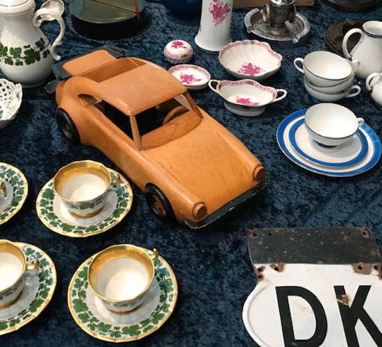 modell eines autos umgeben von porzellan tassen auf dem antikmarkt